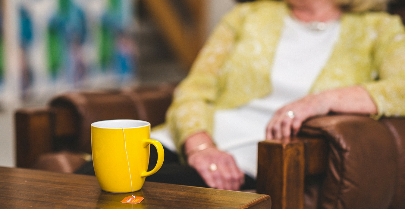 Close up of a yellow cup of tea with a woman sitting in an armchair in the background.